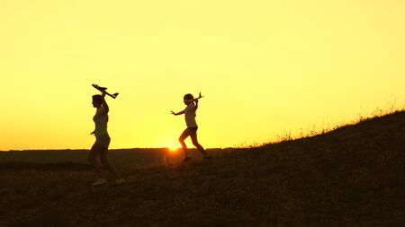 Dreams of flying. Silhouette of children playing on plane. Children run from the mountain with an airplane in hand at sunset. Happy childhood concept. girls play with a toy plane at sunset.