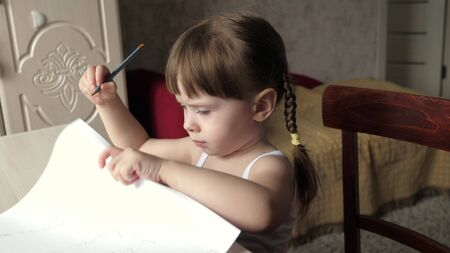 kid draws on sheet of white paper. Cute little artist girl child crayons in a room at a table. focused smart preschool child enjoying creative art hobby at home activity. children development concept Stock Photo
