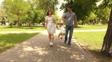 happy child plays with dad and mom holds their hands and jumps. little daughter jumping holding hands of dad and mom in the park. Family concept. Walking with small kid in nature.