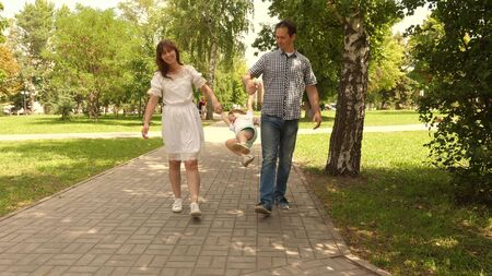 happy child plays with dad and mom holds their hands and jumps. little daughter jumping holding hands of dad and mom in park. Family concept. Walking with small kid in nature.