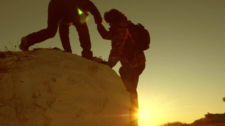 team of climbers climbs a mountain holding out a helping hand to each other. Free woman traveler climb mountain. teamwork of tourists. Travel and adventure in mountains at sunset. Stock Photo