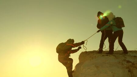 climbers climb mountain on a rope. free woman and man traveler climbs a mountain. teamwork of tourists. travel in mountains at sunset. businessmen insure each other. help in difficult circumstances.
