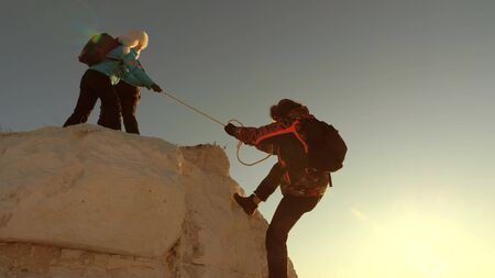 team of climbers climbs a mountain on a rope. free woman helps a male traveler climb a mountain. teamwork of tourists. Travel and adventure in mountains at sunset. businessmen insure each other.