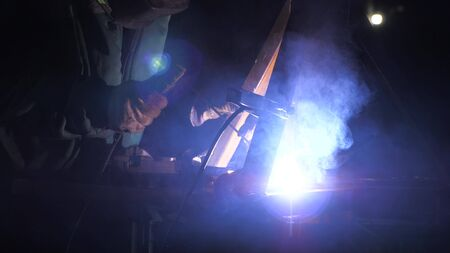 Industrial worker in a protective mask using a modern welding machine for welding metal structures in industrial production at a metal processing plant. bright light and sparks from welding.