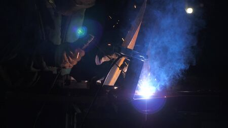 Industrial worker in a protective mask using modern welding machine for welding metal structures in industrial production at a metal processing plant. bright light and sparks from welding.