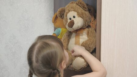 little happy girl actively play with plush toys and teddy bears. the child plays in the children's room. kid loves to play his toys. concept of childhood and family