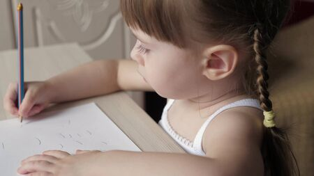 children development concept. child draws on sheet of white paper. Cute little artist girl baby crayons in a room at a table. focused smart preschool kid enjoying creative art hobby at home activity.