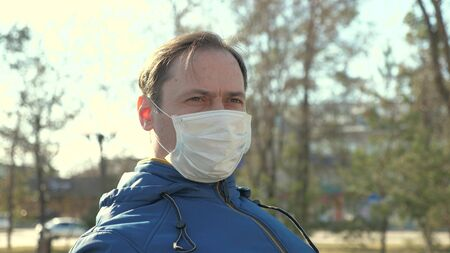 Portrait of male tourist wearing a protective mask on a street in a park. protection against viruses and bacteria. health and safety concept, coronavirus N1H1.health and safety concept. Flu pandemic. Stock Photo