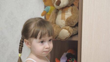 little happy girl actively play with plush toys and teddy bears. the child plays in the childrens room. the kid loves to play his toys. concept of childhood and family