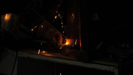 bright light and sparks from welding. Industrial worker in a protective mask using a modern welding machine for welding metal structures in industrial production at a metal processing plant.