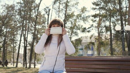 young girl in a protective mask on street. Pandemic Coronavirus. woman tourist in a park on a bench wears a protective mask from viruses. concept health and safety, N1H1 coronavirus, virus protection.