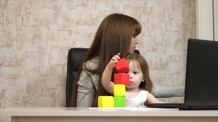 work at home. in the room, mom works at the table with her little daughter at the computer. business woman working in the office on a laptop with a baby in her arms. Female freelance work.