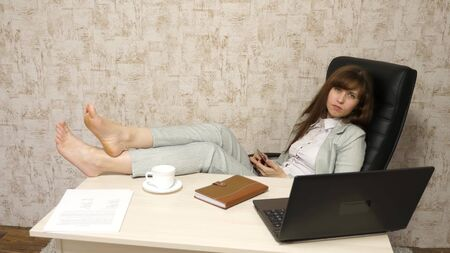 beautiful businesswoman with phone sits in a chair with bare feet on the table resting. girl at work in the office keeps a note on a mobile phone.
