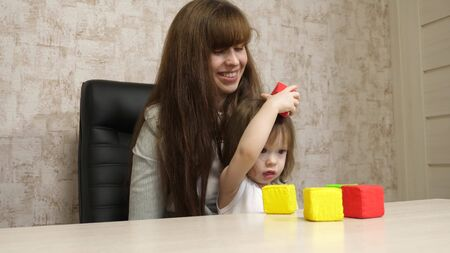 woman works at home with a child. quarantine coronavirus. mother plays with her child in multi-colored cubes at work in office. A busy woman is working and resting with a baby in her arms.