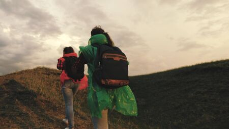 strong and healthy girls travelers travel in colorful raincoats, climb mountain, hold hands, help each other. Free women tourists with backpacks on rise to top of hill, rejoice in victory and jump