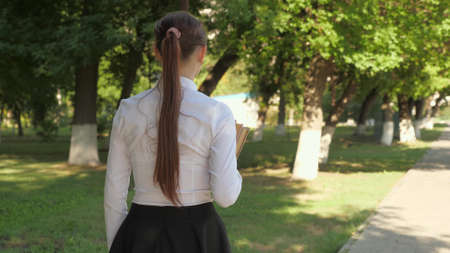 A student walks down the street with textbooks in her hands in the summer park. schoolgirl in the city. girl teenager hurries to school with books.