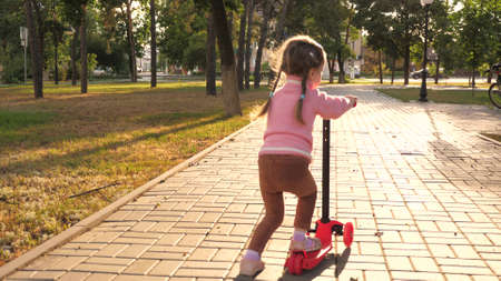 Little girl learns to ride a scooter.