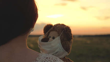 A child holds his beloved teddy bear in a protective mask