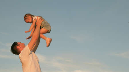 Dad throws up a happy daughter in the blue sky. happy family travels. Father and small healthy child play together, laugh and hug. Baby in arms of parent. Dad day off. concept of a happy family.