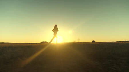 running after sun. training jogging. A healthy beautiful girl is engaged in fitness, jogging in country in sun. Jogger girl breathes fresh air on field. Free young woman runs in summer park at sunset.