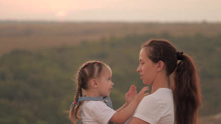 mommy and baby hug. Mom plays with her daughter and shows child sunset. Happy family, mom and daughter in field look at sun. concept of a happy family and healthy children. baby loves mommy Banque d'images