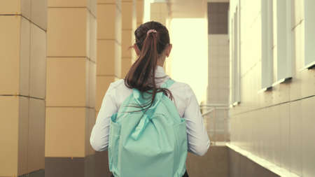 a school girl with a backpack goes down the street to school a beautiful young student goes to class. concept of education. a teenage girl hurries to class.