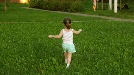 Happy child runs on a meadow in summer on a green grass. cheerful little girl runs across field. concept of happiness. kid plays on the lawn in the summer. Slow motion. baby plays in park in spring.