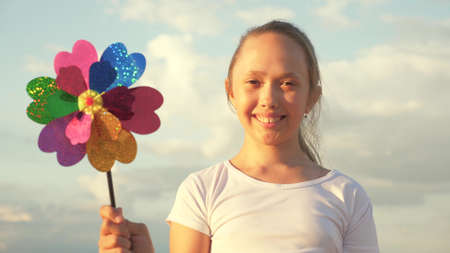 girl playing pinwheel park in slow motion. Happy child playing having fun pinwheel. Happiness vacation childhood children happy family holiday. childhood concept. a child playing in park catches wind