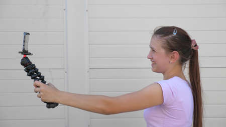 beautiful girl makes selfie outdoors. teenager is photographed on a smartphone using small tripod. young girl blogger leads an online video conference from the city street. modern digital technologies