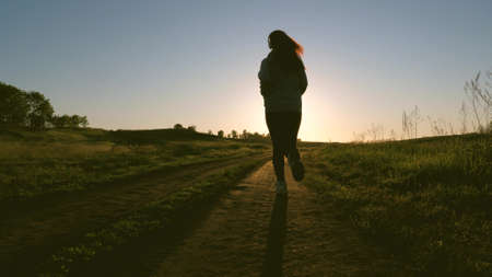 healthy beautiful girl is engaged in fitness, jogging, silhouette. free young woman is training in summer in the park at dawn. Jogger girl breathes fresh air. evening run in beautiful rays of sun. Banque d'images