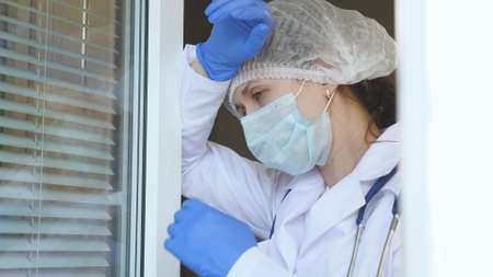 A tired female doctor in protective suit approaches window, takes off her medical mask and hat, closes her eyes from fatigue, breathes fresh air. Hard working day of doctor in hospital.