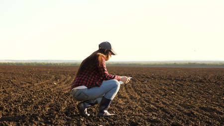 A farmer checks quality of the soil before sowing. woman farmer with a tablet in field holds earth in his hands. girl agronomist checks the quality of sowing grain. business woman checks her field
