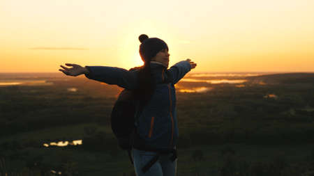 free girl tourist travels in nature alone. young woman traveler with a backpack comes to edge of the peak of sunrise, raises her hands in air and spins, enjoys victory, beautiful dawn and landscape.