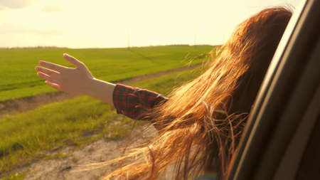 free woman travels by car catches the wind with her hand from the car window. Girl with long hair is sitting in front seat of car, stretching her arm out window and catching glare of setting sun Banque d'images