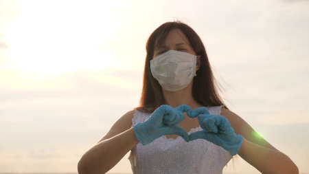 female doctor showing fingers of heart and love for patients. girl in a protective mask and medical gloves shows heart symbol with her hands. young woman loves doctors. pandemic, covid 19
