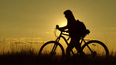 woman cyclist overcomes an obstacle. Healthy young woman tourist goes with bicycle along hillside, enjoying nature, fresh air. free girl travels with a bicycle in sunset. adventure and travel concept.