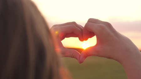 The girl made a beautiful heart from her finger in the rays of the sun. healthy woman making heart shape with hands at sunset. Shining summer sun on your hands. healthy heart concept. Banque d'images