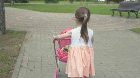 healthy childhood concept. little girl walks in the park with a stroller and a teddy bear. A kid on the street with his favorite toy. the child plays in the playground. Banque d'images