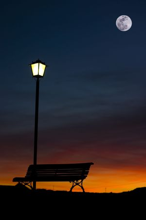 Back-lighting of a streetlamp bench and a at the dusk