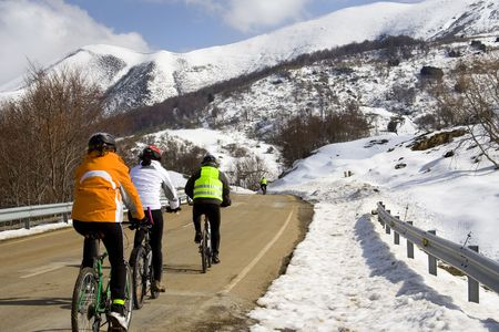 Some friends doing sport with his mountain bikes in the snow of Cantabria, Spain Stock Photo