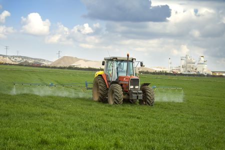 Rural scenic of a tractor working the field. Took in a meadow of the north of Spain. Stock Photo