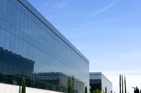Some buildings of a business complex. The windows are mirror type, reflecting other buildings, and a sunny and clear sky. Stock Photo