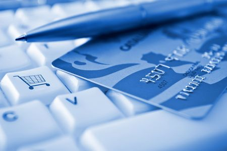 internet fraud: Credit card over a keyboard with a SHOPPING CART conceptual key Stock Photo
