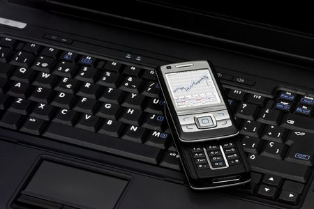 Closeup image of a notebook and a smartphone showing an economic chart Stock Photo