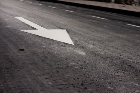 obligation: Traffic sign of obligation printed in the asphalted road. Motion blur is deliberated. The focus is in the arrow. Stock Photo