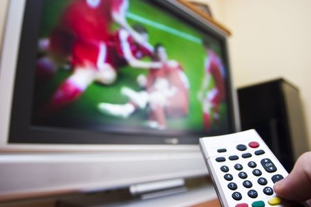 Man with a remote control watching sports on a LCD television Stock Photo