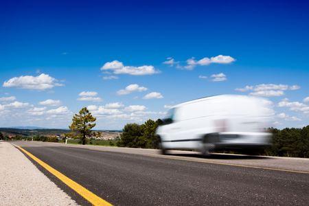 Blanc van dans une route de campagne avec des arbres et un grand ciel bleu ci-dessus