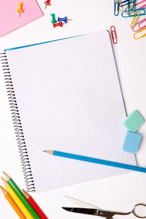 Set of pencils, erasers, post-its and other useful supplies for the school. There is a centered blank notebook for text writing photo