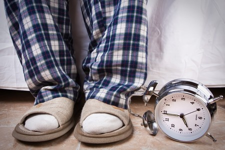 recently: Alarm clock in the floor near an recently awake man Stock Photo