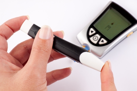 glucometer: Woman pricking her finger for a blood test with a glucometer in the background